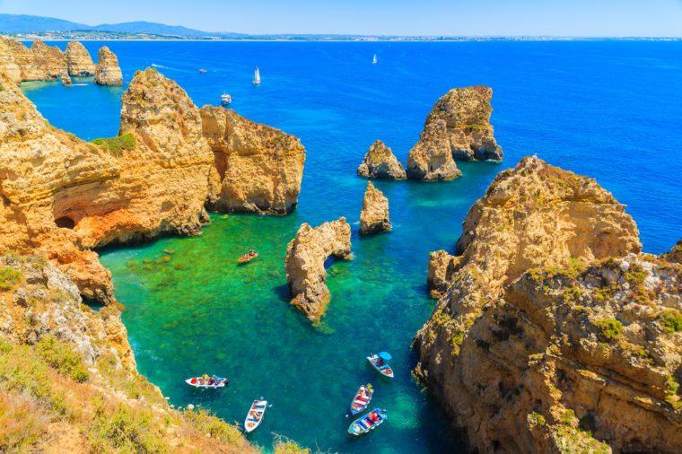 Fishing boats on turquoise sea water at Ponta da Piedade, Algarve region, Portugal