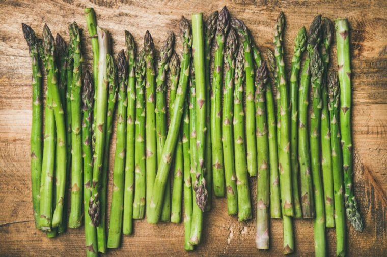 Seasonal harvest produce . Flat-lay of raw uncooked green asparagus in row over rustic wooden background, top view. Local market food concept