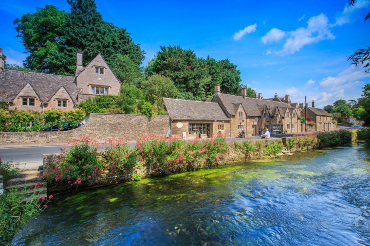 BIBURY, ENGLAND, UK - JULY 9, 2014: Arlington Row traditional Cotswold stone cottages in Gloucestershire on JULY 9, 2014, England. Bibury it the most depicted village in the world.