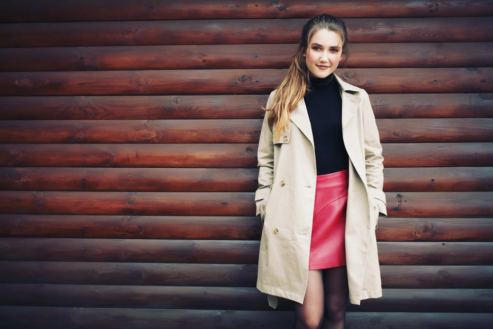 Beautiful young model with ponytail wearing black turtleneck, red leather skirt and trench coat. Professional make-up, hair style and styling. Autumn woman portrait in fall outdoors
