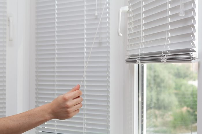 Girls hand raise the white blinds with a cord