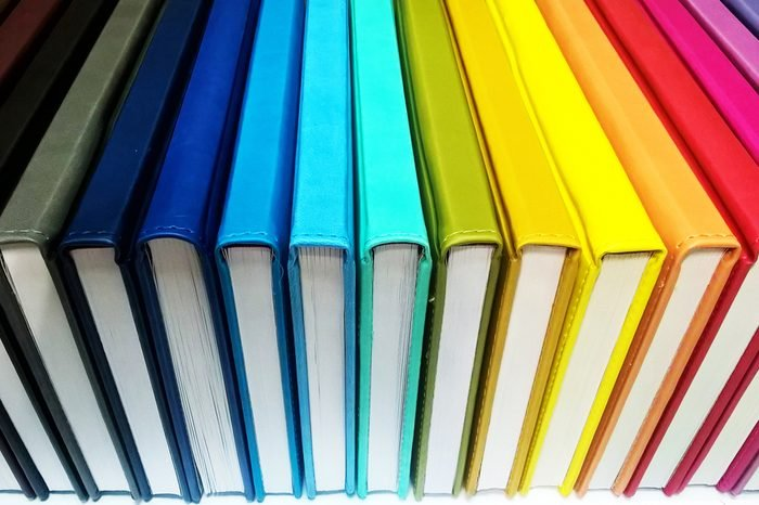 Books. A lot of books with bright covers in one pile isolated on white background. Design element, paper and leather texture. Colorful books on the shelf, close up