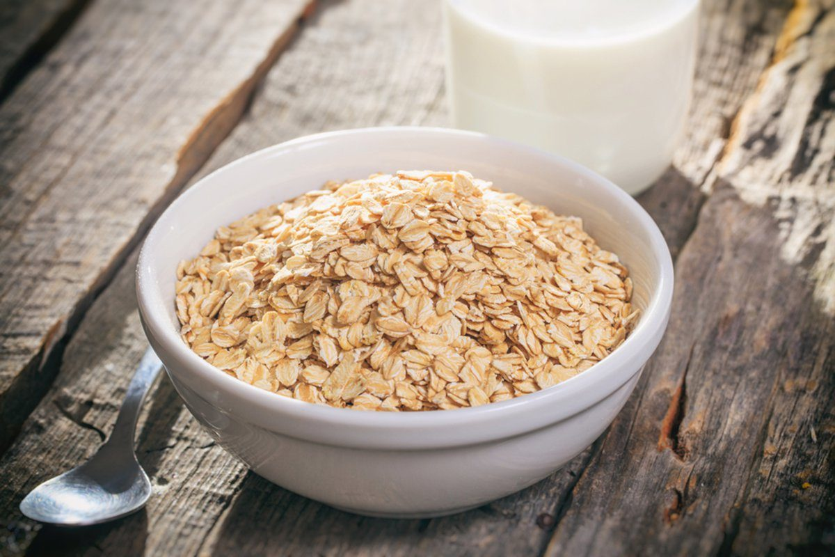 Bowl of oat flakes and glass of milk, on wooden surface.