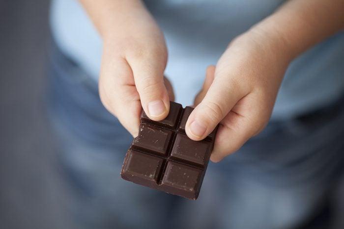 Broken piece of dark chocolate in child's hands.