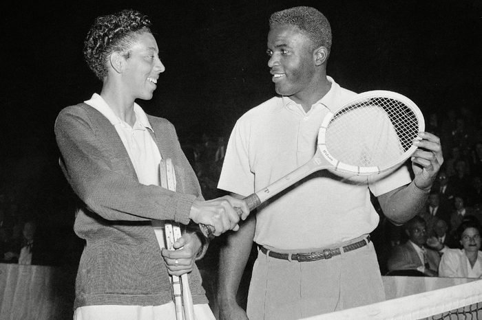 Brooklyn Dodgers' second baseman, Jackie Robinson, gets tennis tips from tennis star Althea Gibson at the celebrity tennis tournament at the 7th Regiment Armory in New York, . The tournament was staged for the benefit of the American National Theater and Academy