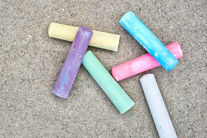 A set of sidewalk chalk composed to leave a large area of the sidewalk for copy.