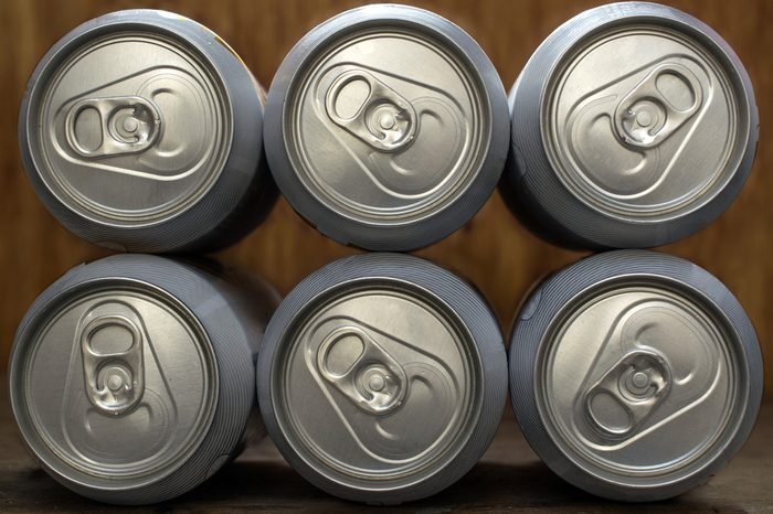 Six frontal organized beer or soda silver aluminum cans, on a wooden background