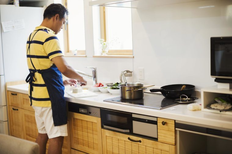 MODEL RELEASED Family home. A man in a blue apron preparing a meal with his son.