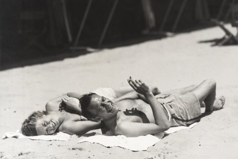 Happy couple sunbathing on beach