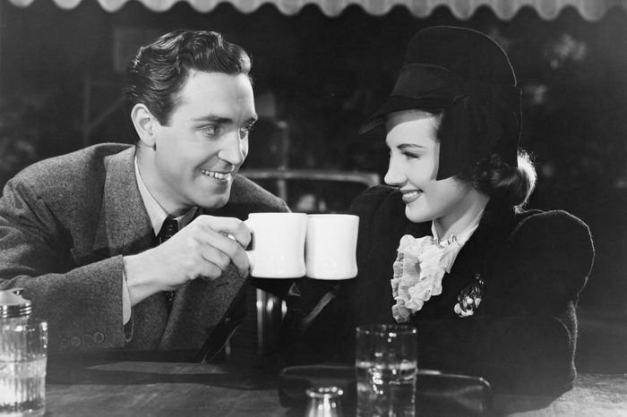 Couple toasting with mugs