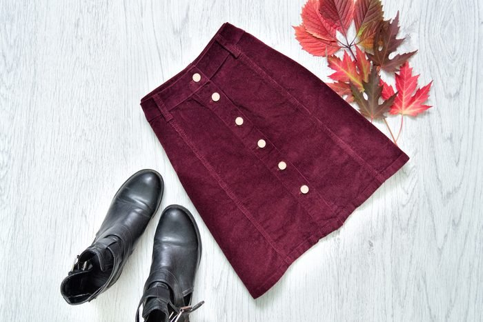 Burgundy suede skirt, black boots and red leaves. Fashionable concept.