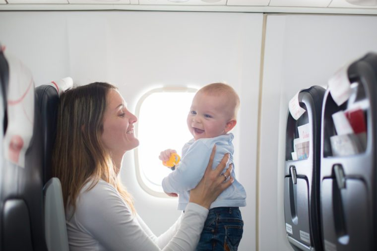 Airline travel tip mom with baby on her lap on a plane