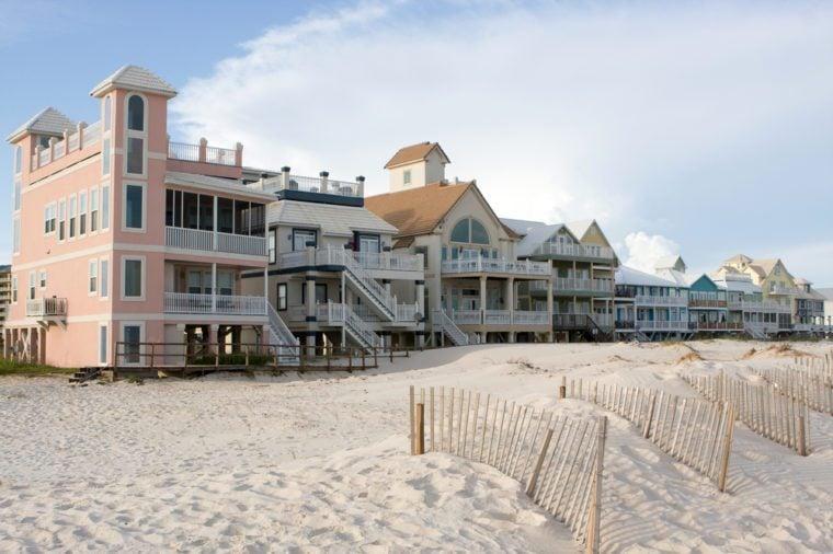 A row of luxury beach homes line the dunes along the Gulf Shores, Alabama coastline.