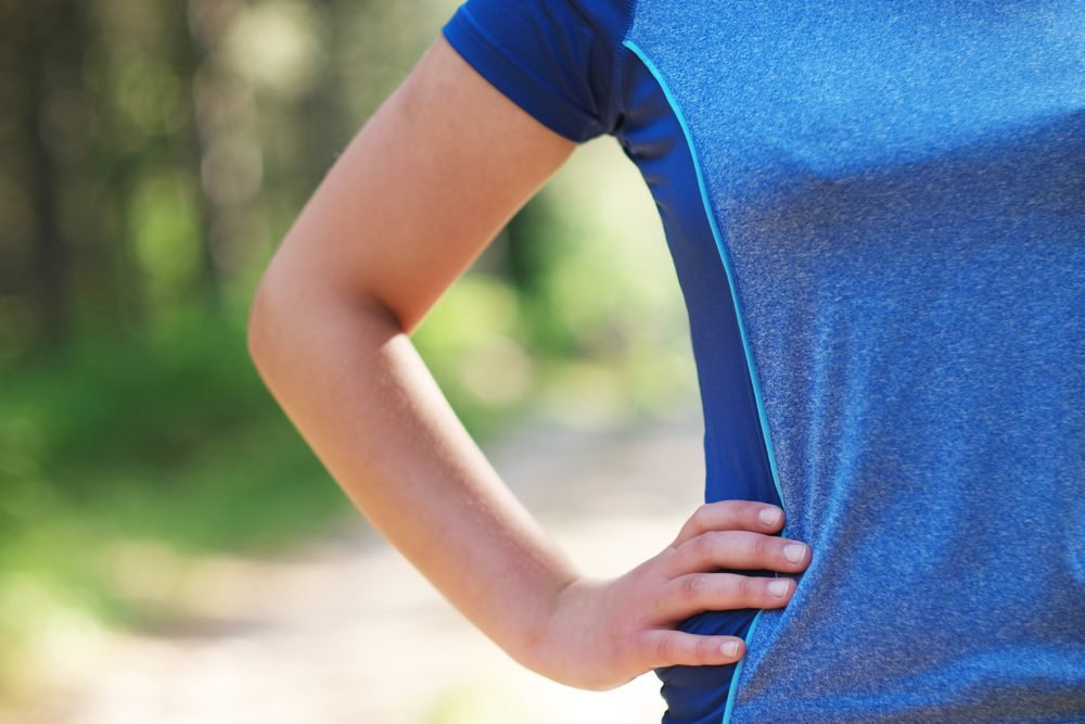 Cropped shot of fit woman in sports wear standing with her hand on hip outdoors, with sun flare.