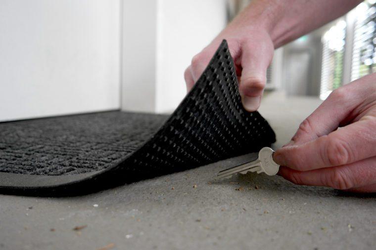 A man's hand lifting edge of a door mat to pick up a key hidden underneath