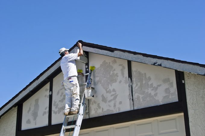 Painter on a ladder uses brown paint.