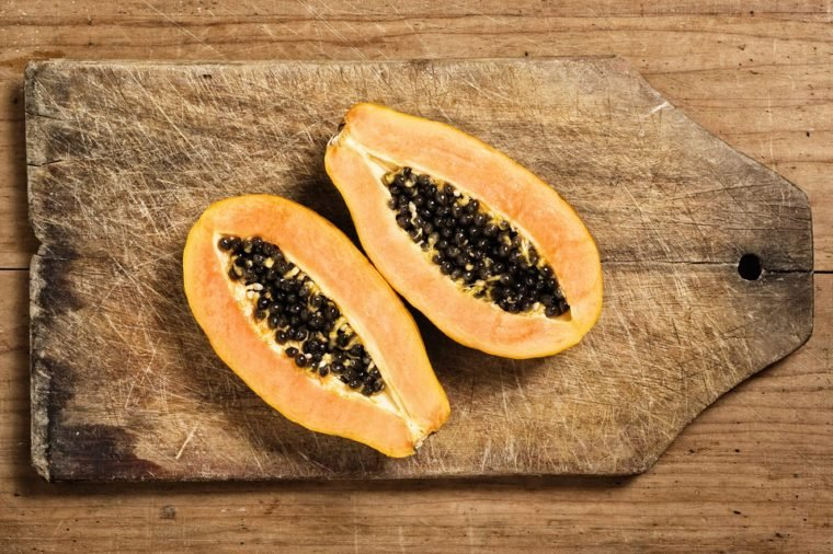 Papaya fruit sliced on a wooden cutting table
