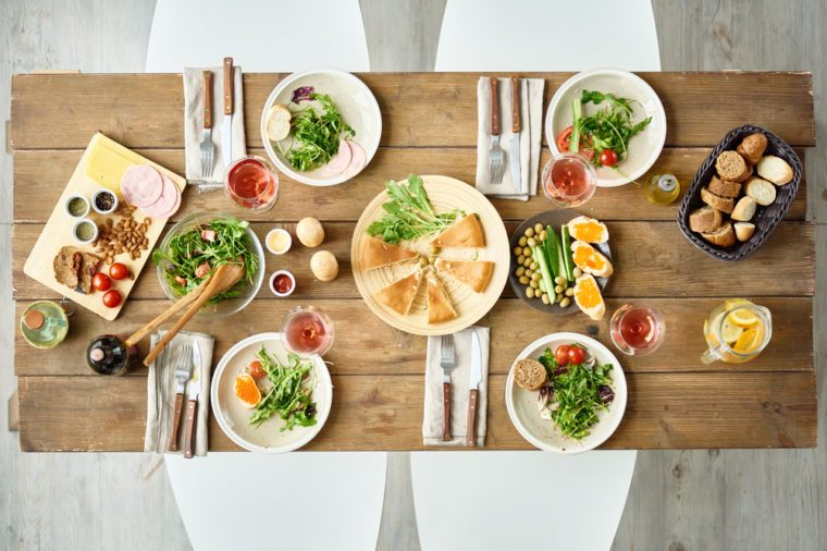 Above view of dinner table with delicious food set for four in cafe or restaurant