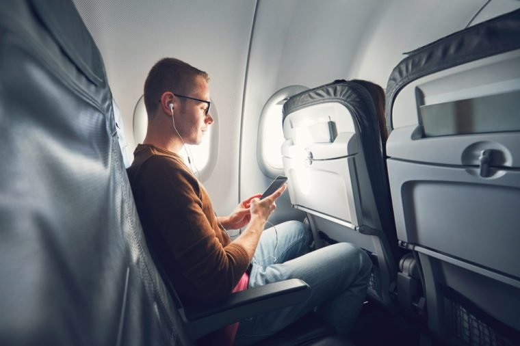 Airline travel tip man listening to phone on airplane
