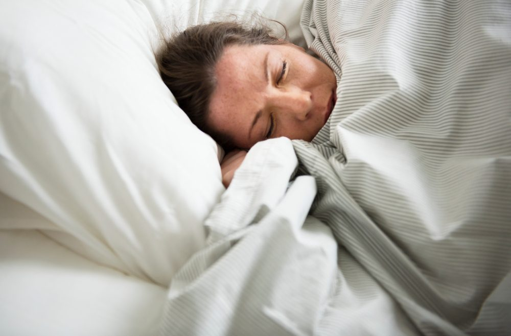 Caucasian woman sleeping on bed