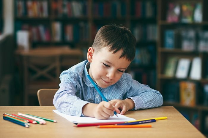 Cute boy doing homework, coloring pages, writing and painting. Children paint. Kids draw. Preschooler with books at home. Preschoolers learn to write and read. Creative boy.