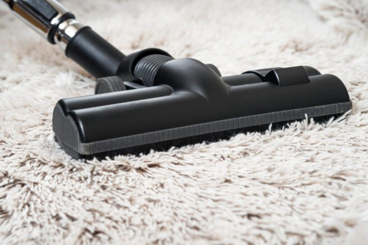 Close up of the head of a modern vacuum cleaner being used while vacuuming a thick pile white carpet.still life dark tone.