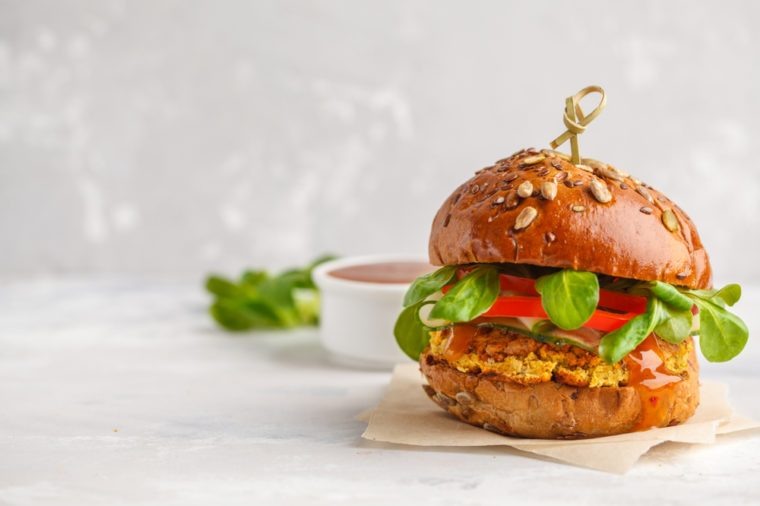 Vegan lentils burger with vegetables and curry sauce. Light background, copy space. Vegan food concept.
