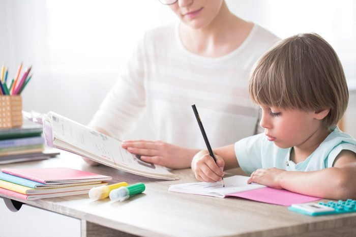 Smart child doing homework at a desk with support of a tutor