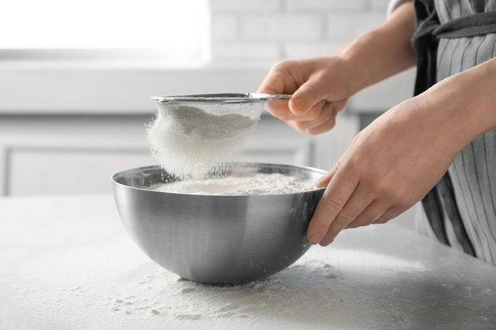 Woman sifting flour into bowl on table