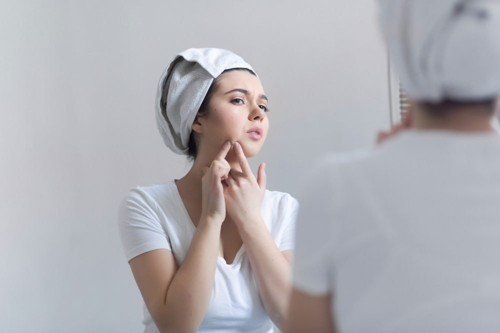 Young woman with acne in bathroom. Portrait of teenager girl looking at the mirror on her skin. Beauty, skin care lifestyle concept.
