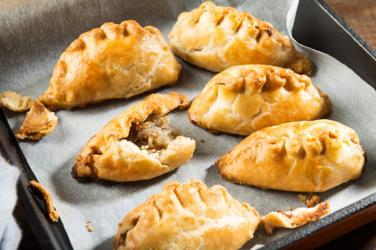 Hot pasties from butter enriched puff pastry filled with minced beef, potato, onions and swede in the iron pan