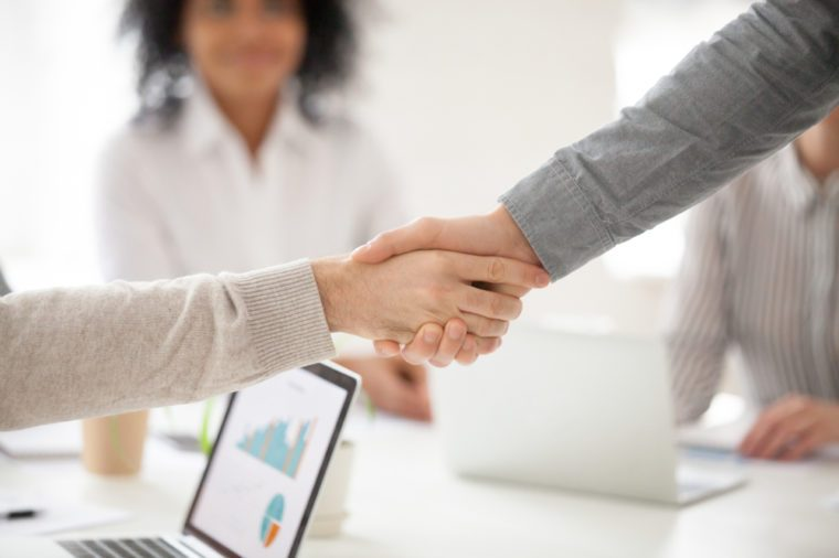 Two business partners handshake at group meeting making online project investment, male hands shake as concept of successful collaboration result or starting partnership after effective negotiations