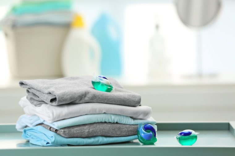 Stack of clothes and laundry pods on table at home