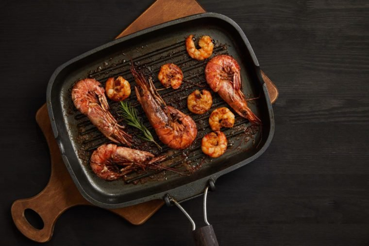 top view of grilled shrimps with rosemary on wooden cutting board on black tabletop