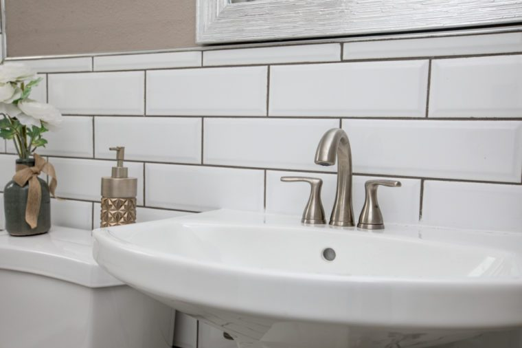 Bathroom sink shot close up with a modern design white subway tile backsplash