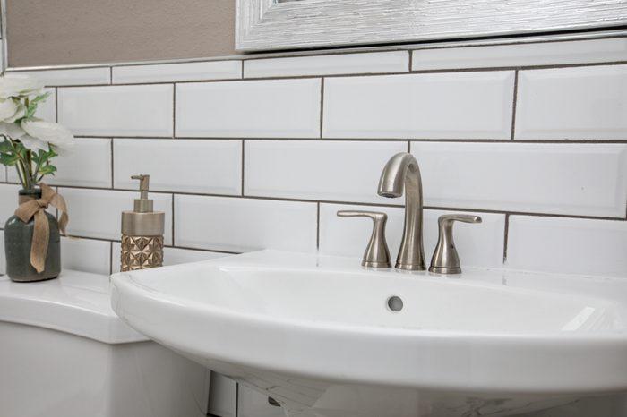 Bathroom sink shot close up with a modern design white subway tile backsplash