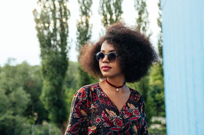 Thoughtful pretty afro-american woman in colorful blouse, wearing sunglasses, looking away. Outdoors.