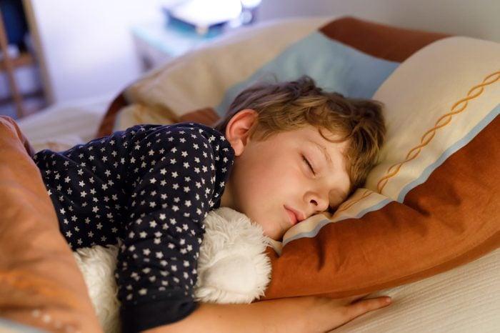 Little preschool kid boy sleeping in bed with colorful lamp.
