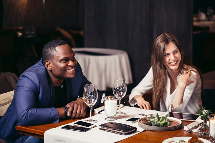 Two interracial young people looking aside at somebody and smiling while siting at the table set for dinner in restaurant