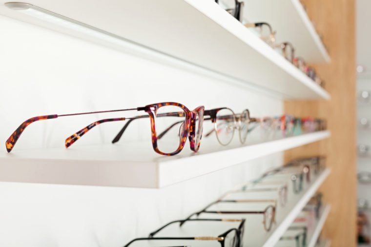 Fashionable corrective eye glasses on a shelf in optical store