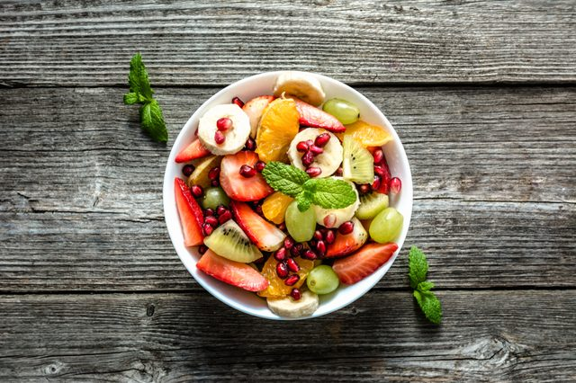 Fresh fruit salad, top view in a bowl on wooden background, vegetarian food concept