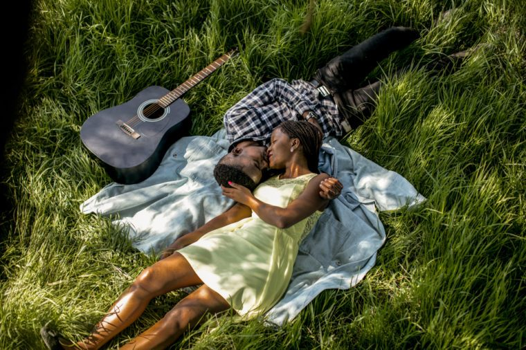 Beautiful fun happy smiling African American couple wearing white shirts laying in grass