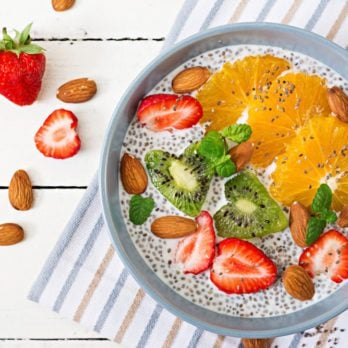 Detox and healthy superfoods breakfast in bowl. Vegan almond milk chia seeds pudding with strawberries, orange and kiwi. Top view. Flat lay