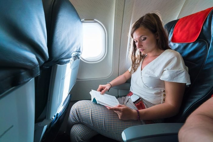 Young woman reading a book on flight near window in airplane