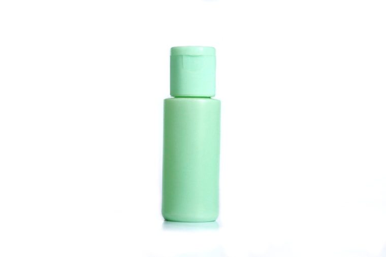 pastel green plastic lotion bottle and white background isolated