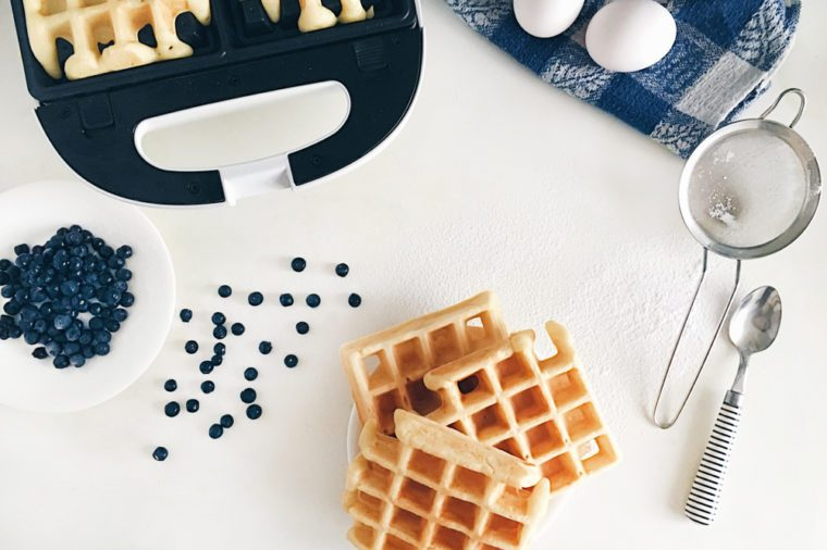 Making Belgian waffles at home - waffle iron, kitchenware and ingredients - fresh blueberry, eggs and flour. Cooking background. Flat lay, top view, copy space