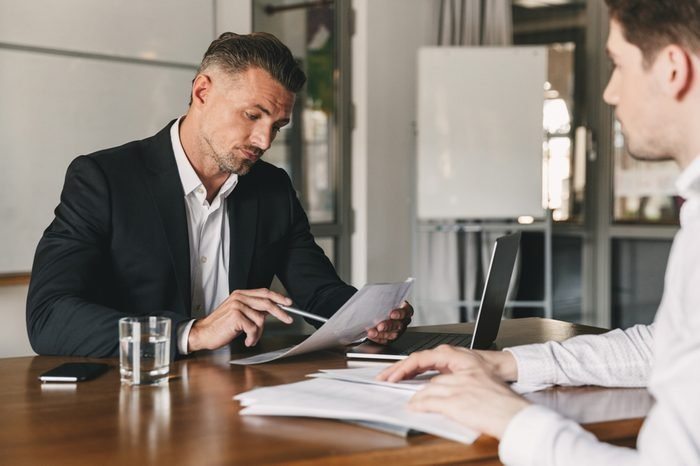 Business, career and placement concept - caucasian businessman 30s negotiating with male employer and reading his resume, during job interview in office