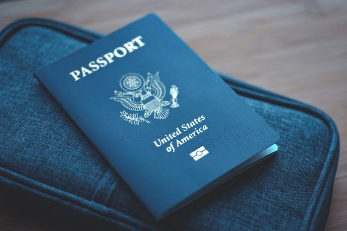 Passport of USA (United States of America) on blue travel wallet, wooden background. Close up.