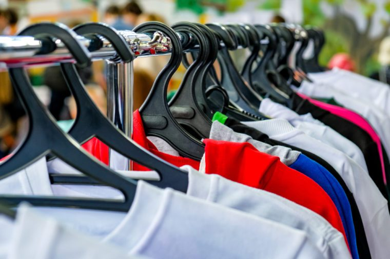 A row of hangers with t-shirts. Sale of T-shirts.