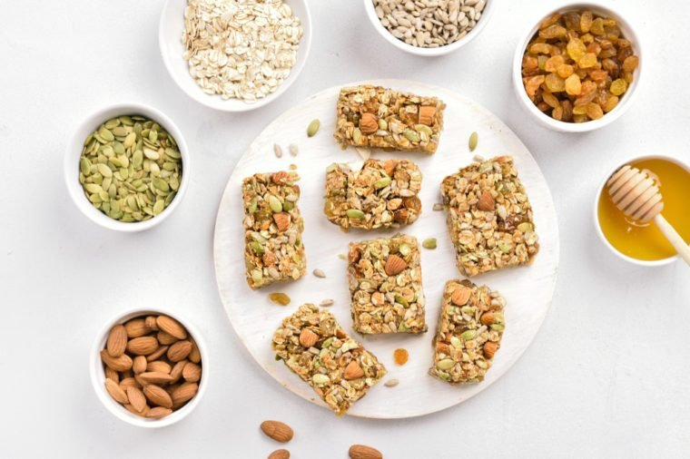 Granola bar on wooden board over white background. Healthy natural snack. Top view, flat lay